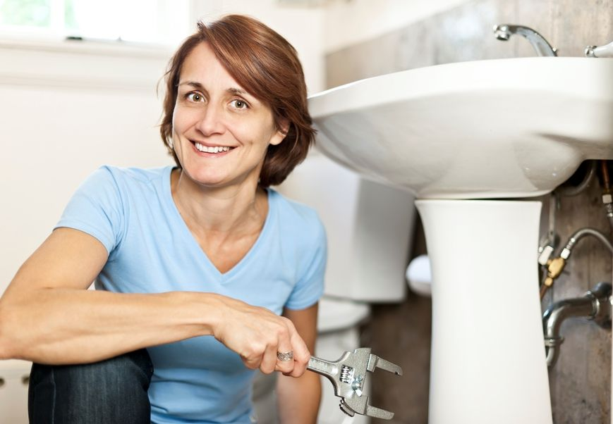 a home owner working on her home's plumbing